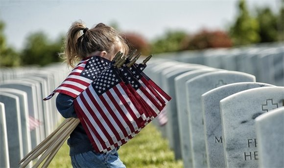 Little girl carrying flags to decorate veterans' graves