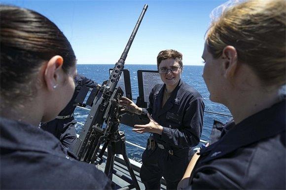 A Sailor trains midshipmen on the .50-caliber machine gun.