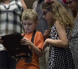 5 year old boy and young girl look at an iPad the little boy is holding