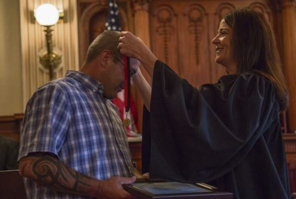 Judge awarding drug court graduate