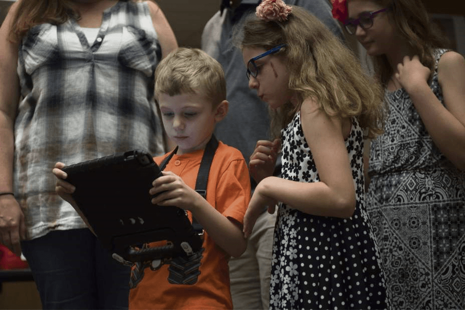 5 year old boy and young girl standing beside each other looking at an iPad the boy is holding