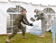 A Soldier from the 28th Military Police Company passes a case of water to a Marine to be loaded onto