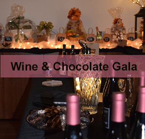 Table with candle, chocolate, wine bottles and raffle baskets