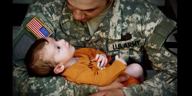 Soldier with young son in his arms
