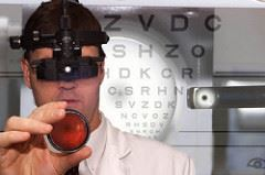 Optometrist with eye chart behind; photo by National Eye Institute, National Institutes of Health