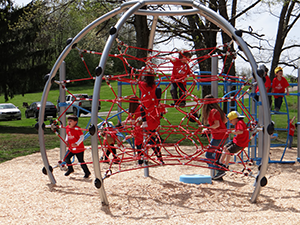 Young children playing on Northmoreland CNX playground equipment