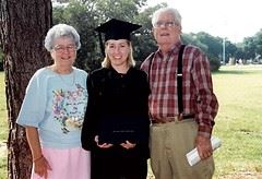 Grandparents with granddaugher in cap and gown graduating from college