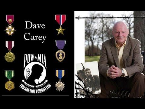 Dave Carey with service awards and photo of him as POW