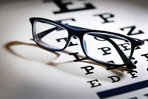 Eyeglasses resting on top of Eye Exam chart