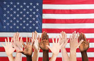 Volunteer hands raised in front of US flag
