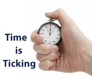Hand holding stopwatch with words Time is Ticking