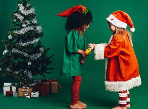 Little girls dressed as an elf and Santa beside Christmas tree